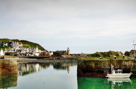 View of a boat moored at Portpatrick harbour in southwest Scotland,with calm reflections in the water on a summers day Stock Photo - 20502887