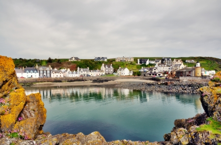 slipway: Tranquil view of Portpatrick harbour in southwest Scotland,lined with pretty houses and framed by lichen covered rocks in the foreground