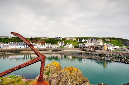 slipway: Picturesque view of Portpatrick harbour in Scotland, with lichen covered rocks and a rusty anchor in the foreground