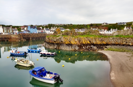 Tranquil view of colourful boats bobbing on the water in Portpatrick harbour, southwest Scotland,with a curving sandy shore Stock Photo - 20671025