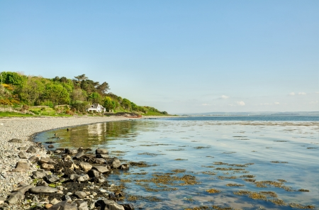 Sweeping view of the shingle beach with foreground rocks at Drumantrae Bay, Dumfries and Galloway, on a beautiful summer day Stock Photo - 20884905