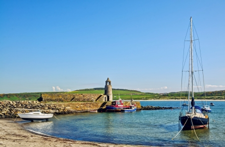 dumfries and galloway: Picturesque view of the beach with a lighthouse and boats at Port Logan, Dumfries and Galloway, on a beautiful summer day