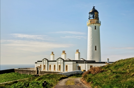 dumfries and galloway: View of the lighthouse and associated buildings set against a blue sky, on the Mull of Galloway in South West Scotland