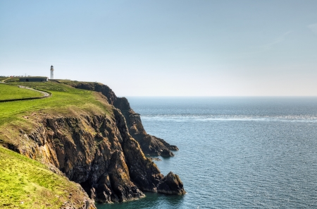 View of a lighthouse on the cliffs jutting into the sea on the Mull of Galloway, South West Scotland on a summer day Stock Photo - 21014022
