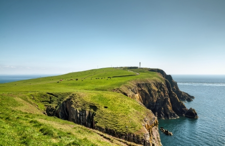 View of a headland with a lighthouse jutting into the sea on the Mull of Galloway, South West Scotland on a summer day Stock Photo - 21014038