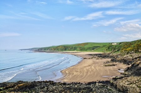 dumfries and galloway: Picturesque view of the curving Killantringan Bay in Dumfries and Galloway, Scotland, with  waves breaking onto the sandy beach