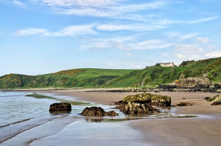 Rocks on the sand at Killantringan Bay in Dumfries and Galloway, Scotland, with waves rippling onto the beach on a beautiful summer day  Stock Photo - 21933952