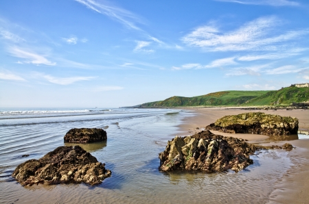 dumfries and galloway: Rocks on the sand at Killantringan Bay in Dumfries and Galloway, Scotland, with waves rippling onto the beach on a beautiful summer day  Stock Photo