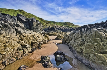 Barnacle encrusted rocks and a small pool on the shore at Killantringan Bay in Dumfries and Galloway, Scotland Stock Photo - 21933955