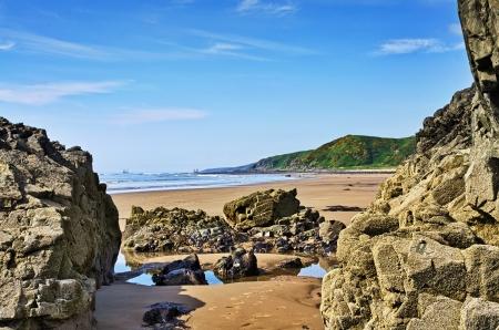 Jagged rocks framing a view of the sea and a grassy headland at Killantringan Bay in Dumfries and Galloway, Scotland
