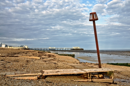 Groynes and a post on the shingle beach at Worthing, West Sussex, with the pier in the background  Stock Photo - 21933961