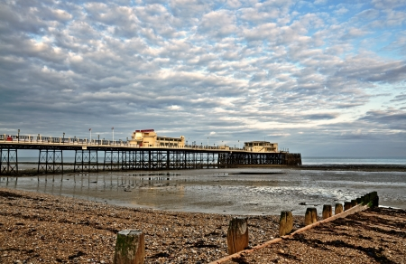 west sussex: View of the Grade 2 listed Victorian pier at Worthing, West Sussex, built in 1862, with shingle beach and  wooden groynes
