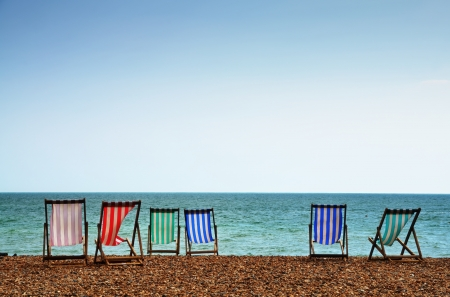 Colourful striped deckchairs on the shingle beach at Brighton, East Sussex, on a summer day