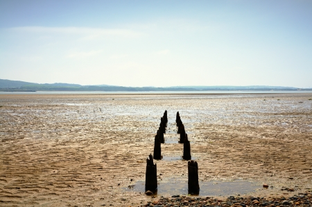 Two lines of weathered wooden posts heading out to sea in Morecambe Bay near Millom Stock Photo - 23086279