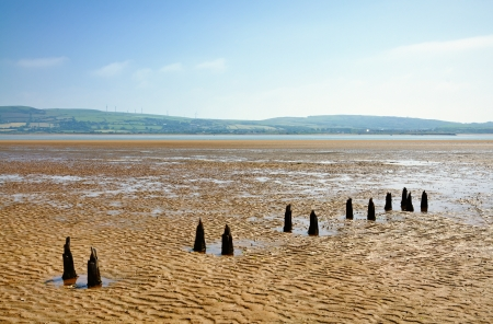 Parallel weathered wooden posts in the sand at Morecambe Bay near Millom Stock Photo - 23086280