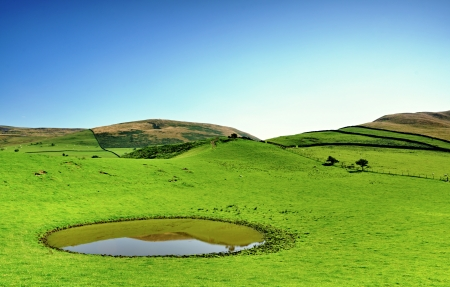 View of a field with circular dew pond on a summers day in the Pennines, England Stock Photo - 23086290