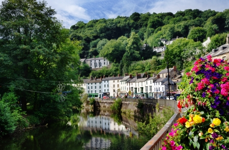 View of the River Derwent flowing through Matlock Bath in Derbyshire with trees and flowers