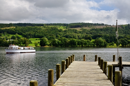 View of a boat passing a jetty on Coniston Water in the English Lake District, Cumbria Stock Photo - 23862192