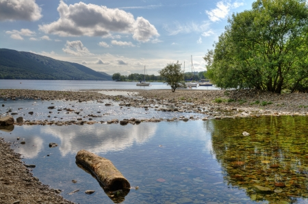 Log in the shallow water by the shore of Coniston Water in the English Lake District, Cumbria Stock Photo - 23865420