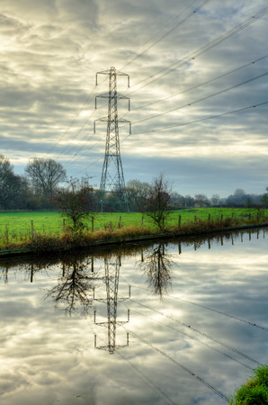electricity pylon: View of an electricity pylon set against clouds and reflected in a canal