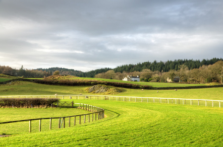 horse racing: Cartmel racecourse with a house, fields and woods in the background Stock Photo