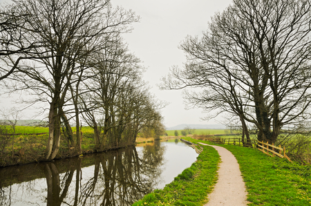 recedes: Lancaster Canal and towpath with trees reflected in the water on a winter day