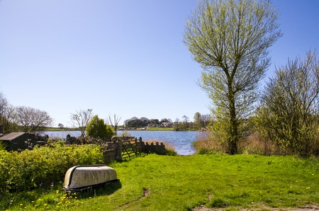 upturned: Scenic view of Urswick Tarn with an overturned boat in the foreground, Ulverstone, Cumbria, England.