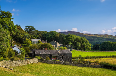 Hamlet with stone barn and group of cottages surrounded by fields,  trees and hills in Cumbria, North of England. Stock Photo