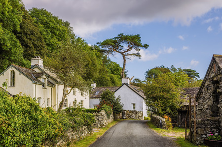 A country lane lined by typical white houses in Cumbria, Northern England.