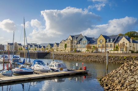 The yacht harbor at Inverkip Marina, Renfrewshire showing the wooden jetty with pleasure boats, yachts and cruisers berthed alongside, background of houses and hotels under blue sky with clouds.