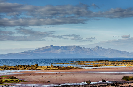 Scenic view of the Isle of Arran pictured over the Firth of Clyde from the coast of West Kilbride in Scotland. Stock Photo
