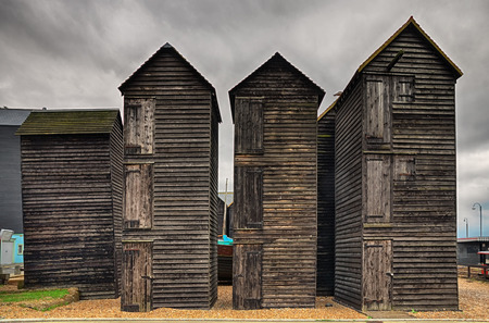 Exterior of tall wooden fishing huts in Hastings, East Sussex.