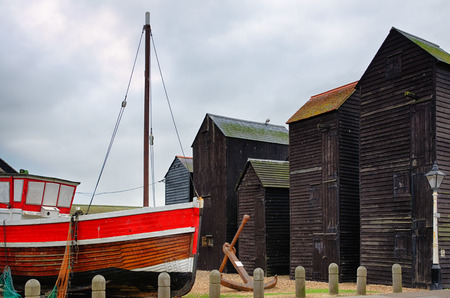 Closeup of a painted fishing boats with wooden huts in the background.