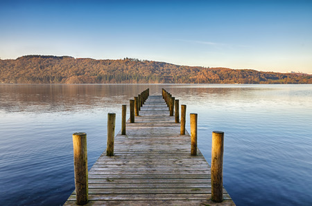 Perspective view of a wooden jetty on Windermere in the English Lake District, on a sunny, calm morning.