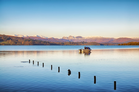 langdale pikes: Two people fishing from a small boat on Windermere, in the English Lake District, with the Langdale Pikes in the distance and wooden posts in the foreground.