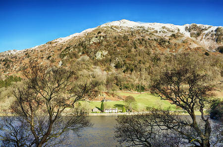 View of a snow capped Nab Scar across Rydal Water in the English Lake District. Stock Photo