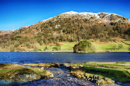 Snow capped Nab Scar and Rydal Water in the English Lake District on a sunny day.