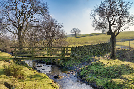 A wooden footbridge and ford crossing a small stream surrounded by rural countryside  in Cumbria, Northern England.