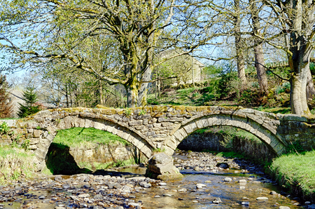 A 13th Century packhorse bridge crossing the stream in Wycoller, Lancashire, Northern England.