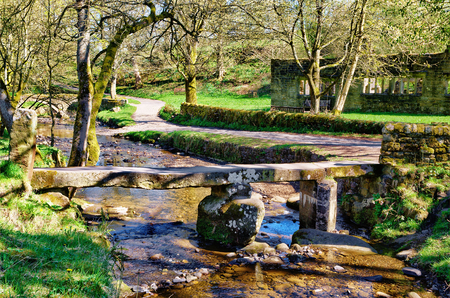 The Clapper bridge in the picturesque village of Wycoller, Lancashire, Northern England. It consists of a single stone slab across Wycoller Beck.
