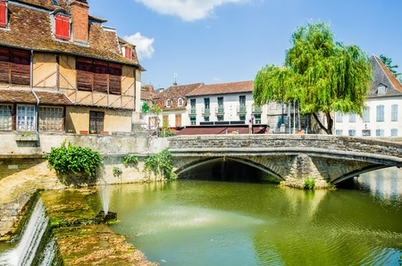 A scenic view of the Fench town of Salies-de-Bearn, with an old house and bridge by a weir.