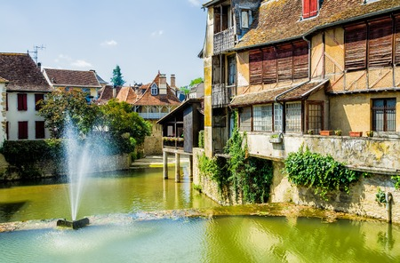 A view of the French town of Salies de Bearn, in the Pyrenees-Atlantiques, with old houses above the river. Stock Photo