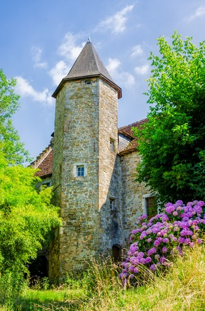 The tower of a traditional church in Salies de Bearn, South West France, surrounded by flowers and greenery.