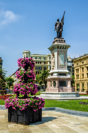 Flowers and a statue in the Picturesque square De Okendo Plaza, in San Sebastian, Northern Spain.