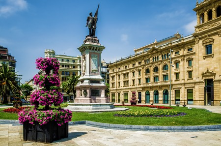 san sebastian: Flowers and a statue in the Picturesque square De Okendo Plaza, in San Sebastian, Northern Spain.