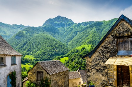 pyrenean: Rustic builidings in the French Pyrenean village of Aydius, with a backdrop of wooded mountains. Stock Photo