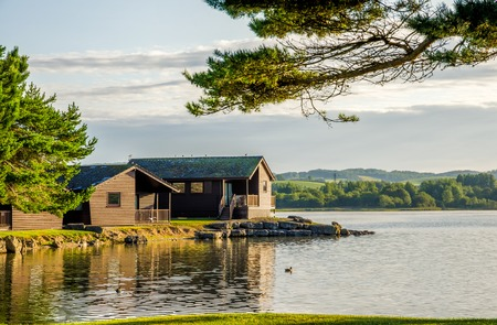 A peaceful scene of wooden holiday lodges bwside a still lake