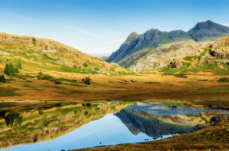 langdale pikes: Landscape in Blea Tarn in the English Lake District with the Langdale Pikes in distance on sunny day.