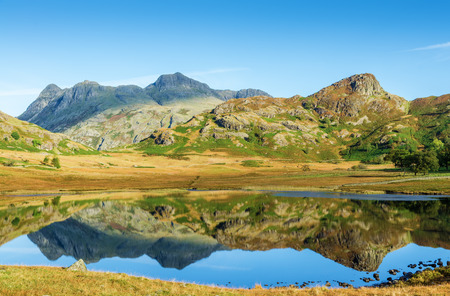districts: Langdale Pike reflection in clear lake at Blea Tarn in The English Lake District in Cumbria, UK on sunny day.