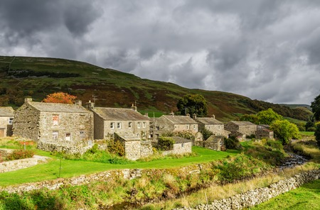 cottages: Rustic stone cottages in the village of Thwaite in North Yorkshire, England on stormy overcast day with rolling green hills. Stock Photo
